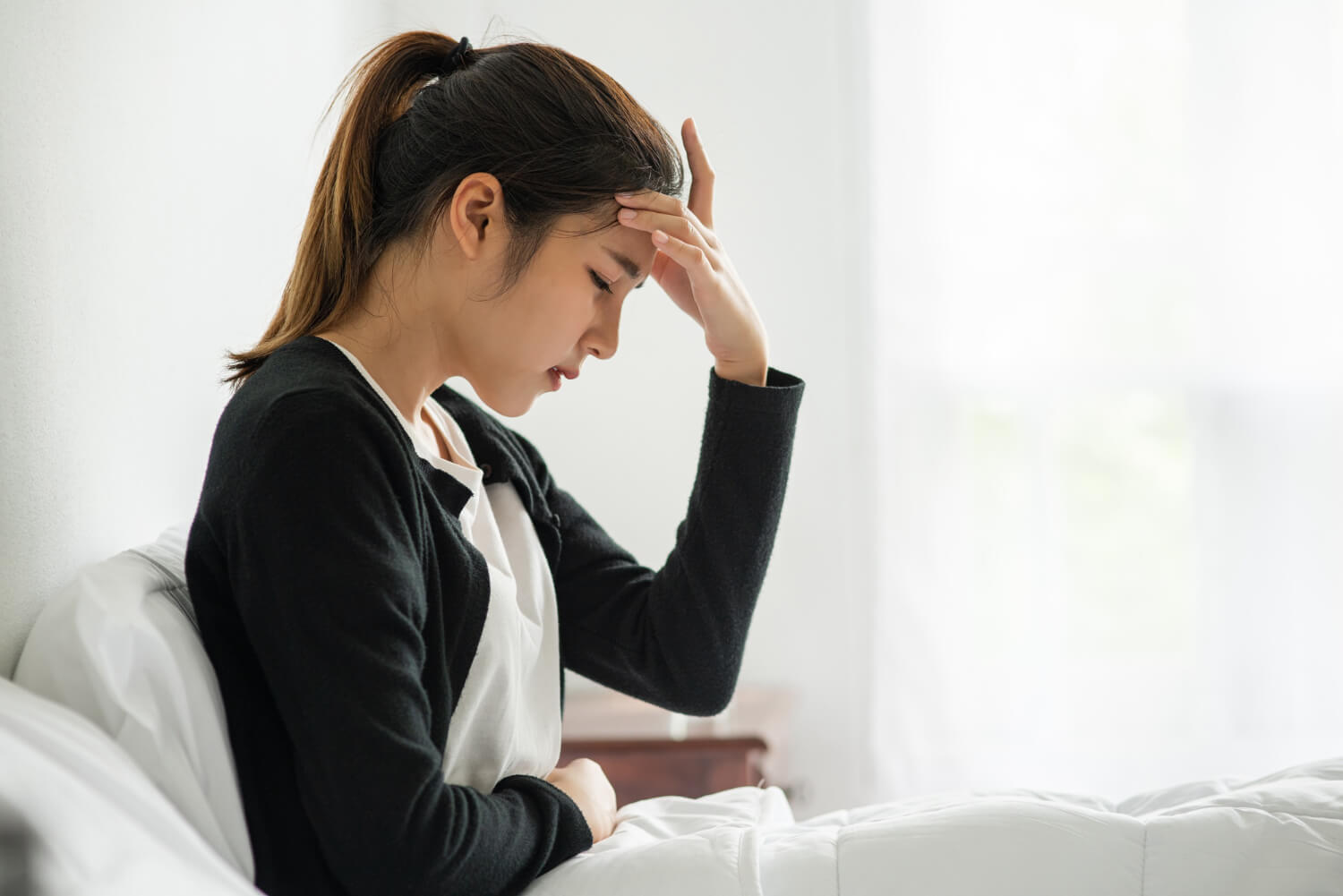 sick-woman-had-headache-hands-touched-her-head-bed