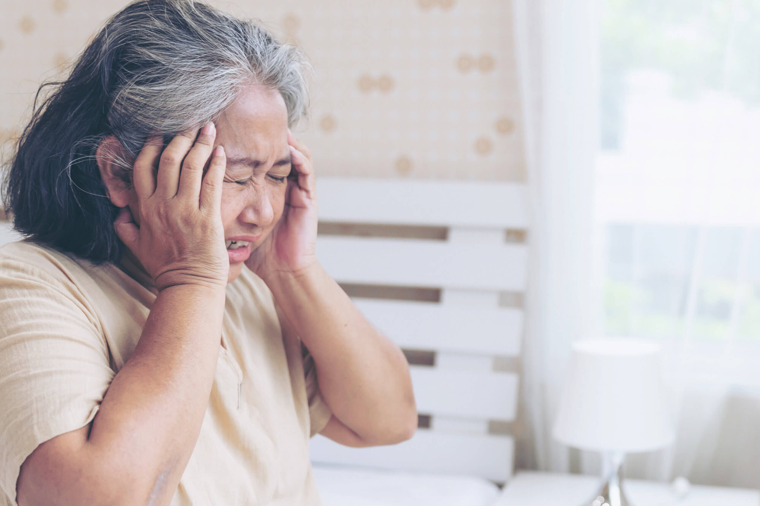 Elderly patients in bed, Asian senior woman patients headache hands on forehead - medical and healthcare concept